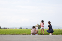 田んぼのそばで遊んでいる家族の後ろ姿 10802000103| 写真素材・ストックフォト・画像・イラスト素材|アマナイメージズ
