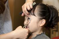 美容室でビューラーを使って睫毛をあげている女の子 10802000115| 写真素材・ストックフォト・画像・イラスト素材|アマナイメージズ