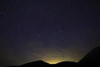街明かりに浮かぶ山並みと夜空に星