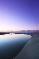 夜明けの空に月と浜辺に小川