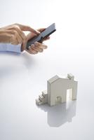 スマートフォンとミニチュアの家 10826000460| 写真素材・ストックフォト・画像・イラスト素材|アマナイメージズ