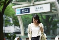 駅の前に立つ女性