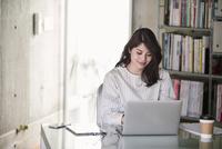 オフィスでノートパソコンを開き仕事をする女性