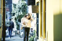 ビルの前を歩く女性 10827001046| 写真素材・ストックフォト・画像・イラスト素材|アマナイメージズ