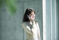 ビルの前に立ちスマートフォンを持つ女性