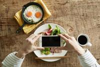 スマートフォンで料理の写真を撮る女性 10827001179| 写真素材・ストックフォト・画像・イラスト素材|アマナイメージズ