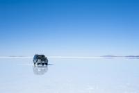 ウユニ塩湖と鏡張の水面を走る車