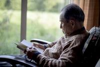 窓辺で読書をするシニア男性