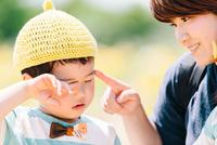 お花畑で目をこする少年と母親 10901000075| 写真素材・ストックフォト・画像・イラスト素材|アマナイメージズ