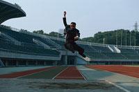 走り幅跳びをするビジネスマン