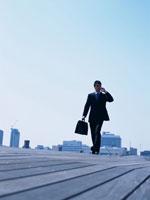歩きながら携帯電話で話すビジネスマン