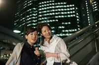 夜のビル街と2人の女性