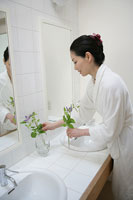 洗面台に花を添える女性