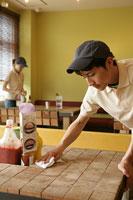 カフェのテーブルを掃除している男性