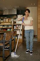 カフェの店内を掃除している女性