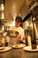 レストランの厨房でデザートを盛付ける女性