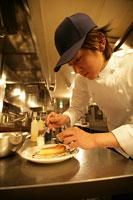 レストランの厨房でデザートを盛付ける男性