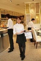 レストランで料理を運ぶ女性スタッフ