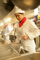 レストランの厨房で料理をする女性