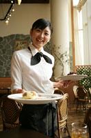 レストランのホールで料理を運ぶ女性