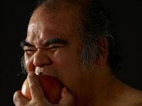 リンゴをかじる中年男性
