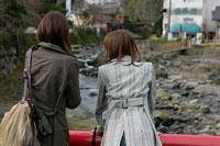 橋の上の後姿の女性二人