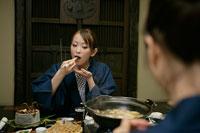 浴衣を着て食事をする女性