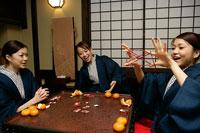 コタツでゲームをする女性