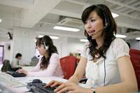 パソコンを使いながら話す女性オペレーター