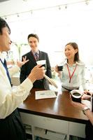 コーヒーを飲むビジネスマンとビジネスウーマン