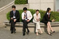 携帯電話を持つビジネスマンとビジネスウーマン