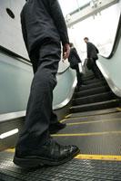 エスカレーターに乗るビジネスマンの足元