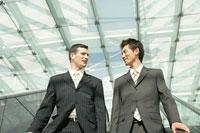 エスカレーターに乗る二人のビジネスマン