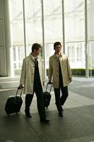 スーツケースを持って歩く二人のビジネスマン
