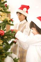 クリスマスツリーの飾り付けをする姉妹