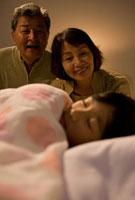 孫の寝顔を見る祖父母