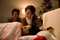 クリスマスプレゼントを枕元に置く両親