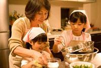 料理をする祖母と姉妹