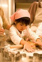 麺棒で生地を延ばす子供