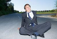 道路に座り込むビジネスパーソン