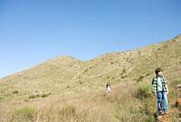 岩に立つ少年と草原の少女