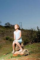 岩に腰掛ける少女