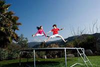 トランポリンで飛ぶ少年少女