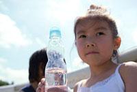 ラムネのボトルをもつ女の子