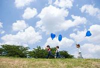 風船を持って走る子供たち