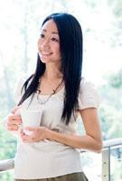 テラスでコーヒーカップを持つ女性