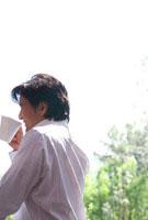 テラスでコーヒーを飲む男性