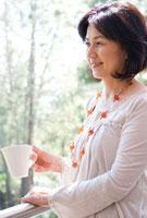 テラスでコーヒーを飲む女性