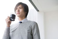 ベランダでコーヒーを飲む男性