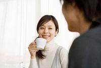 コーヒーカップを持った笑顔の女性
